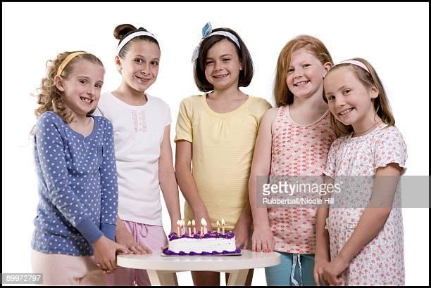 five girls around a birthday cake