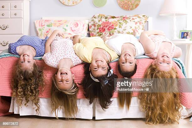 five girls on a bed upside down