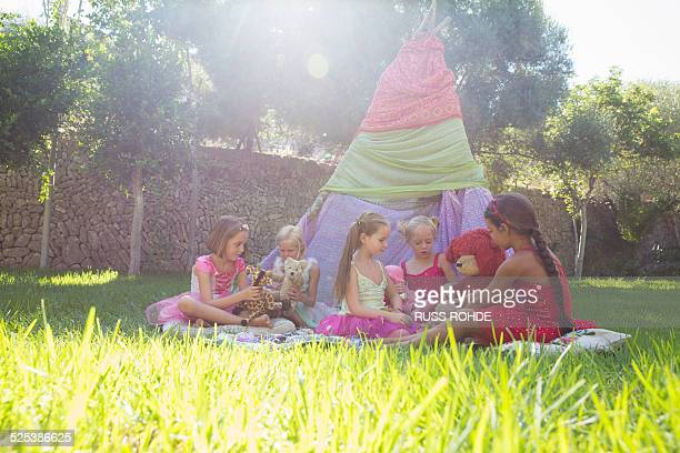 Five girls playing with teddy bears in front of teepee