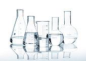 Five glass flasks with a clear liquid, isolated