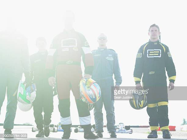 Five go-cart racers with helmets on track, portrait, low angle view