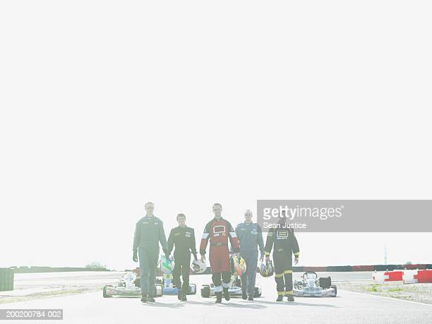 Five go-cart racers with helmets walking on track, portrait