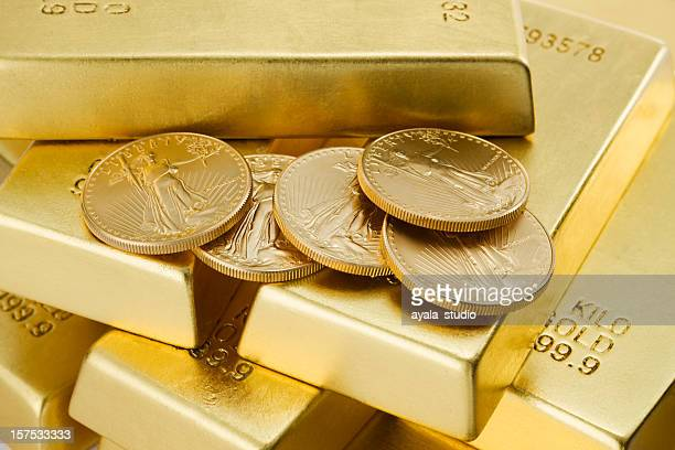 Five gold coins on top of lots of gold bars
