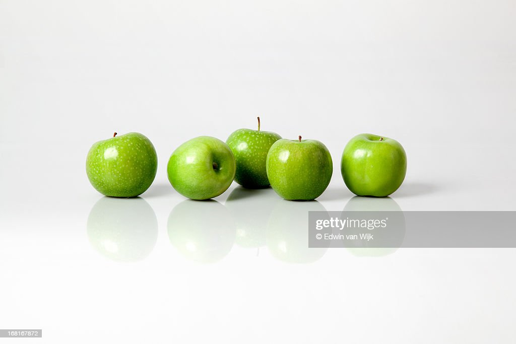 Five green apples on a light grey background : Stock Photo