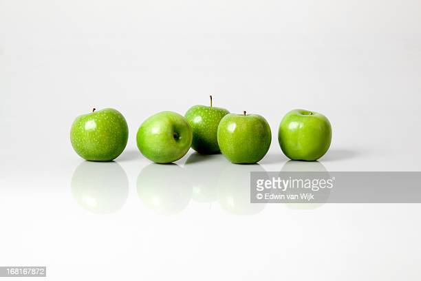 Five green apples on a light grey background