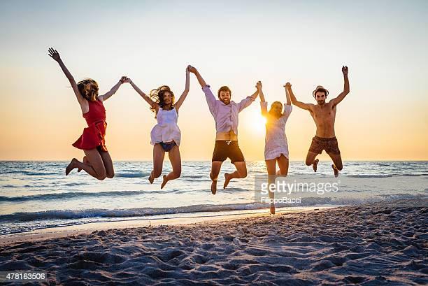 Cinq amis heureux de sauter sur la plage pour l'été
