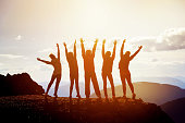 Five happy friends having fun standing with raised arms on mountain top at sunset time