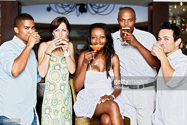 Five happy young people socializing over drinks