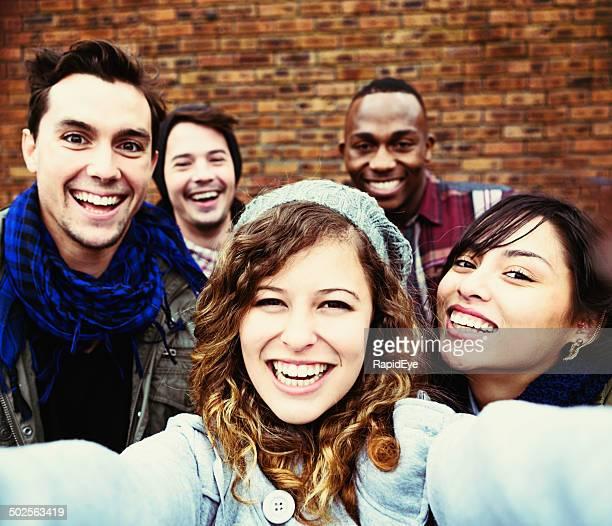 Cinq jeunes souriant heureux prendre selfie