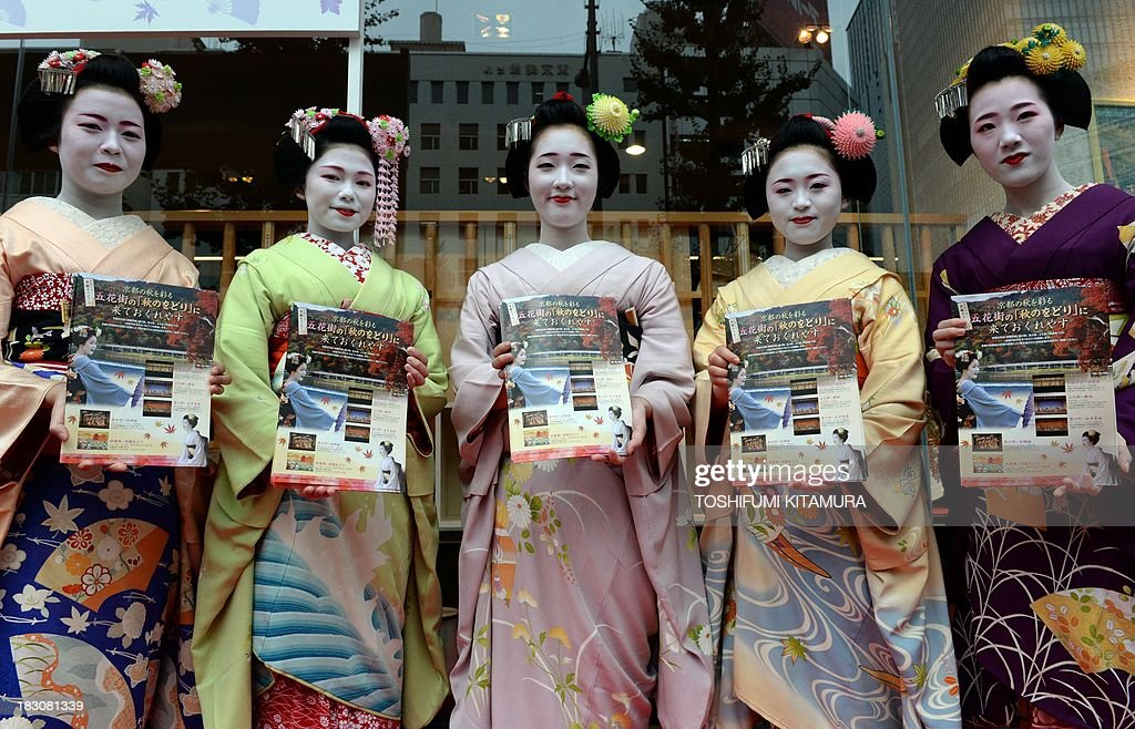 Five 'Maiko,' or apprentice geishas, (from L-R) Ichitomi from Gion Kobu, Toshitomo from Miyagawa cho, Chizu from Ponto cho, Ichimari from Kami Shichiken and Tomitae from Gion Higashi, display Kyoto sightseeing leaflets during their 'We're alive and well, Kyoto' campaign in Tokyo on October 4, 2013. As Kyoto prepares itself for the biggest sightseeing season of autumn, the girls lent their charms to lure back tourists to the 1,200-year-old city after a big typhoon flooded some of scenic spots there three weeks ago.