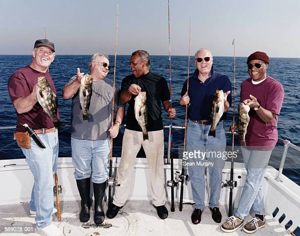 Five mature men holding catch (calico bass) on deck of boat