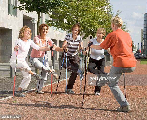 Five mature women doing exercises with walking sticks