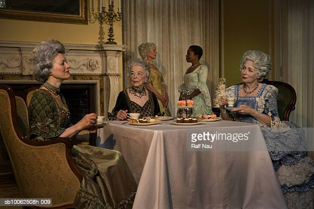Five mature women sitting at table and having tea