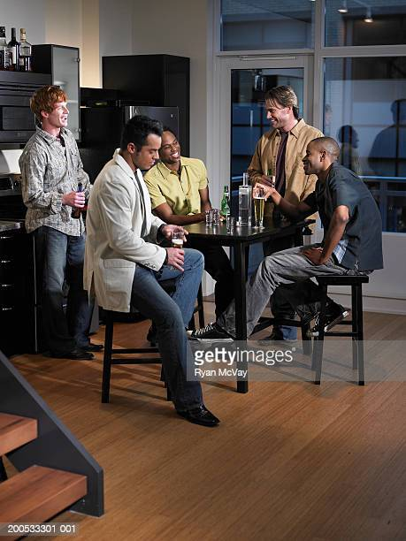 Five men drinking beer in domestic kitchen, laughing, night