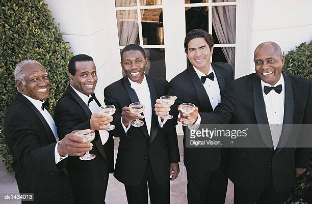 Five Men in Tuxedos Making a Toast Outdoors at a Wedding Reception