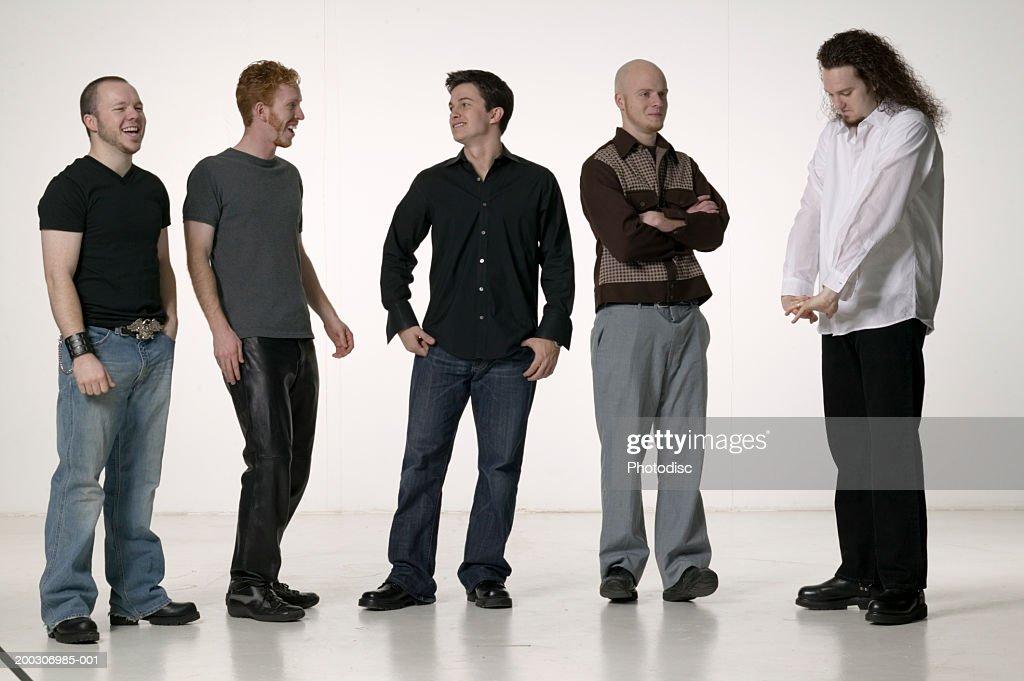 Five men standing, posing in studio