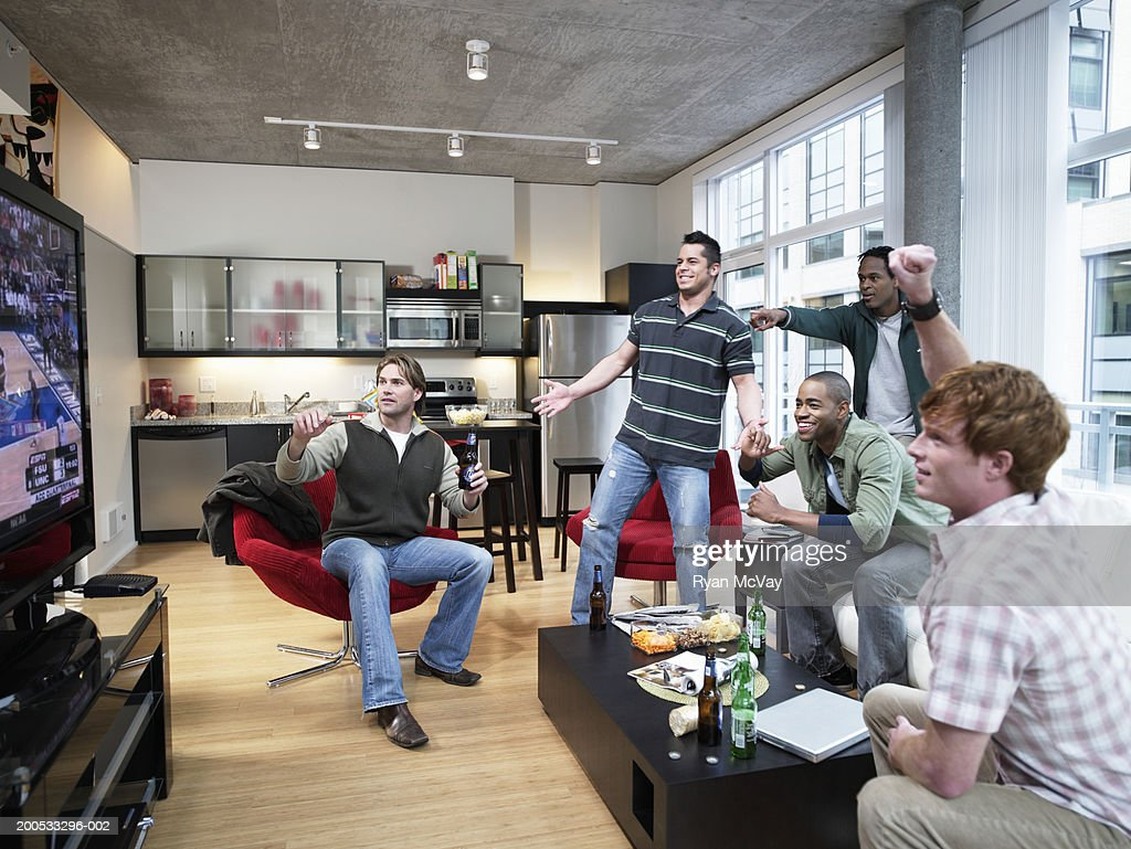 Five men watching sports on television, cheering : Stock Photo