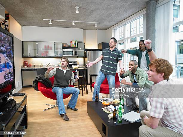 Five men watching sports on television, cheering