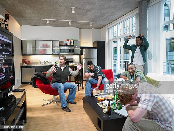 Five men watching sports on television, laughing and gesturing