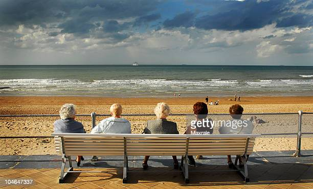 Five Old ladies sitting on bench chilling out near sea