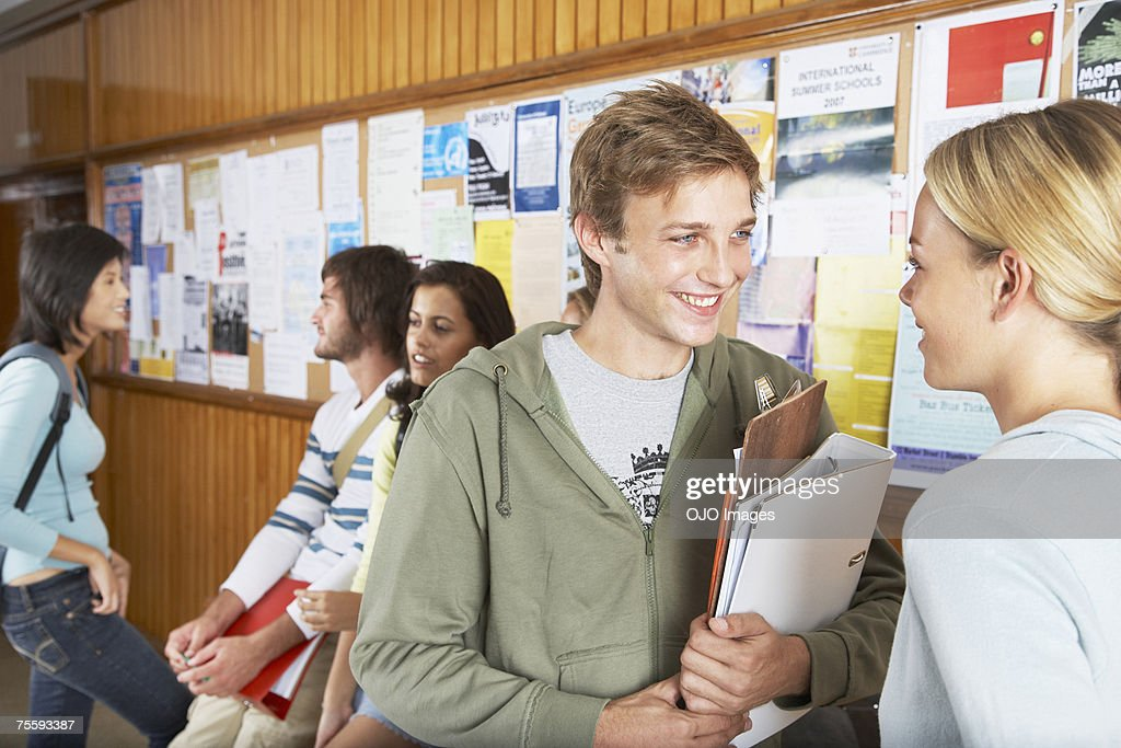 Five people by a bulletin board : Stock Photo
