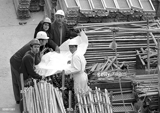 Five people examining blueprints in construction site, portrait, b&w
