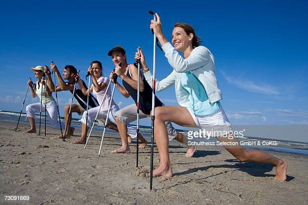 Five people exercicing on beach