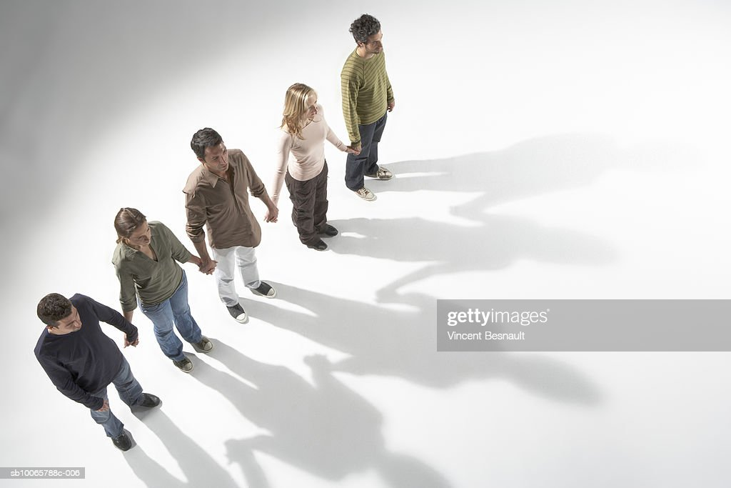 Five people holding hands, standing in row