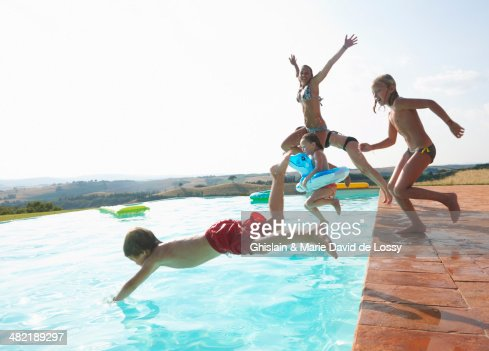 Five people jumping into swimming pool