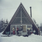 Five people relaxing on the terrace of the glassfronted triangular Skaal House in the Stowe Mountain ski resort in Stowe Vermont 1962 The property is...