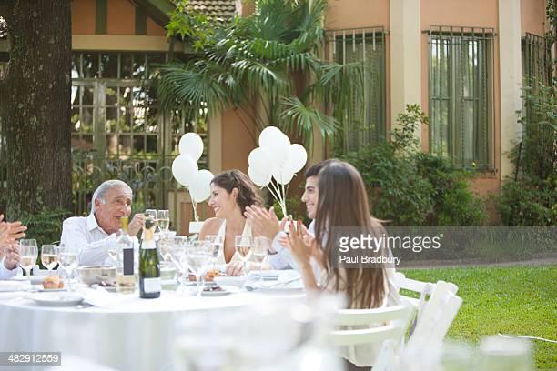 Fünf Personen am Tisch sitzen im Freien und Lächeln Klatschen