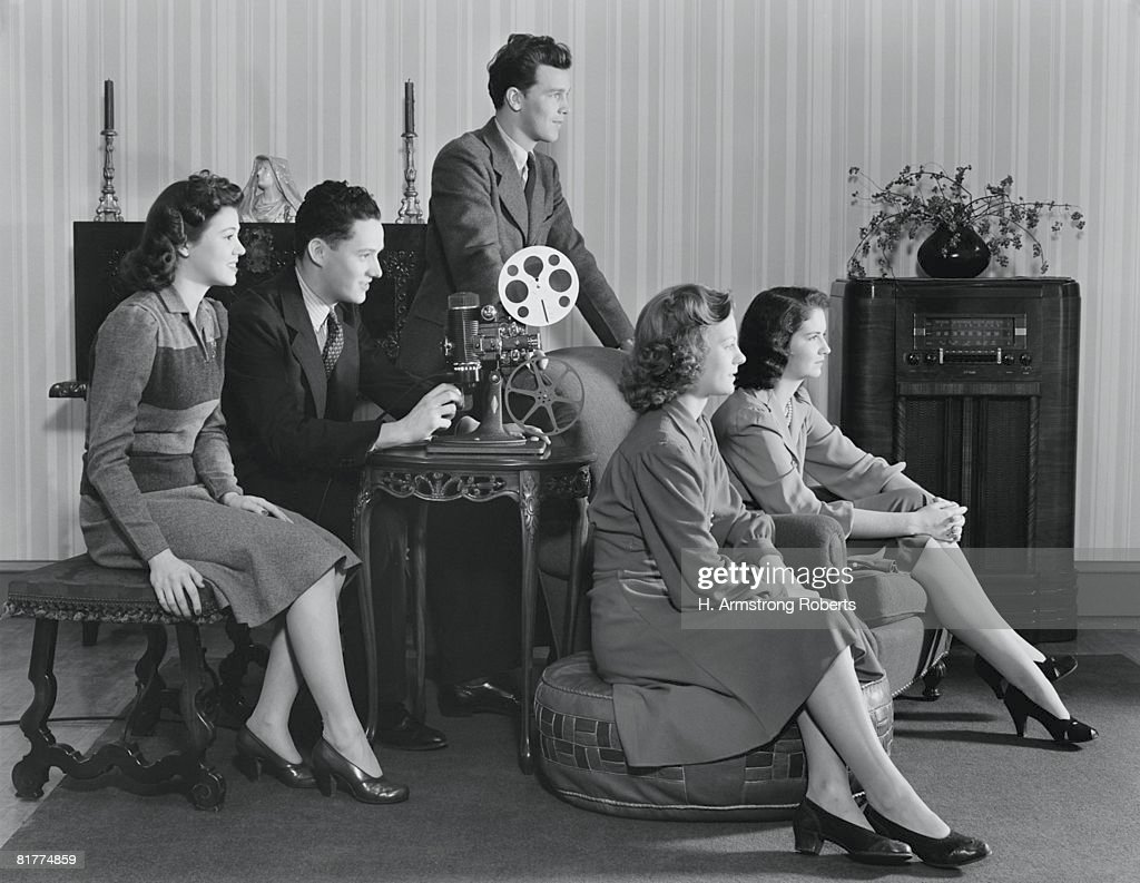 Five people watching home movies, seated around projector, looking toward screen. : Stock Photo
