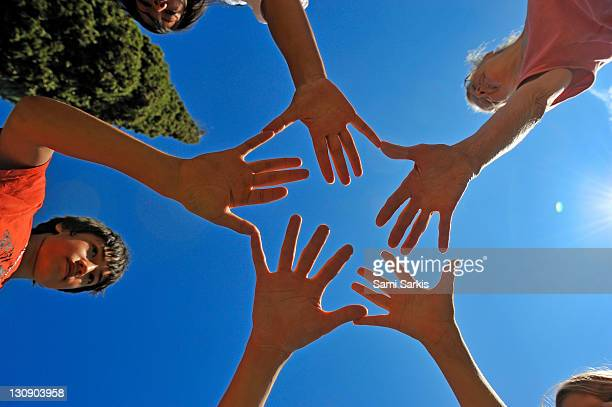 Five people with hands in circle, palms upward