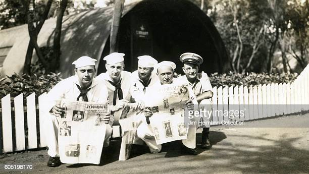 Five sailors squatting in front of white picket fence and holding open newspapers Quonset hut in background