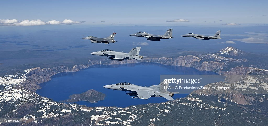 A five ship formation of two F-15 Eagles, two F-18 Super Hornets and an F-16 Fighting Falcon fly over Crater Lake, Oregon, during the Sentry Eagle Excercise.
