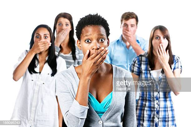 Five shocked young people with hands over their mouths