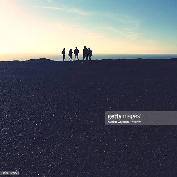 Five silhouette people at distance on beach
