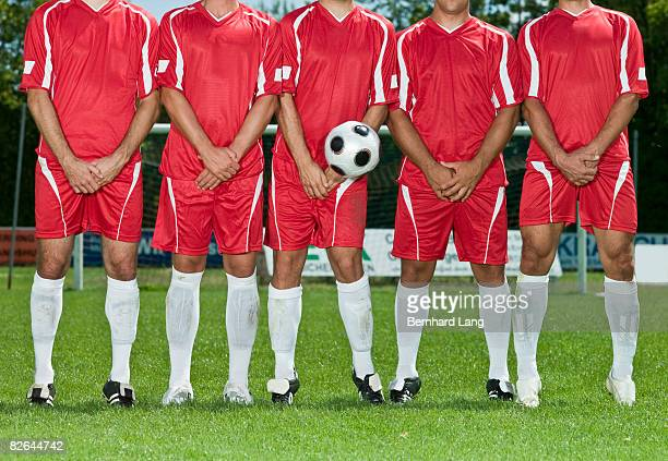 Five soccer players forming defence wall