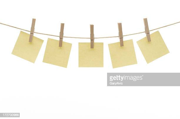 Five square yellow blank notes hanging by clothespins on clothesline