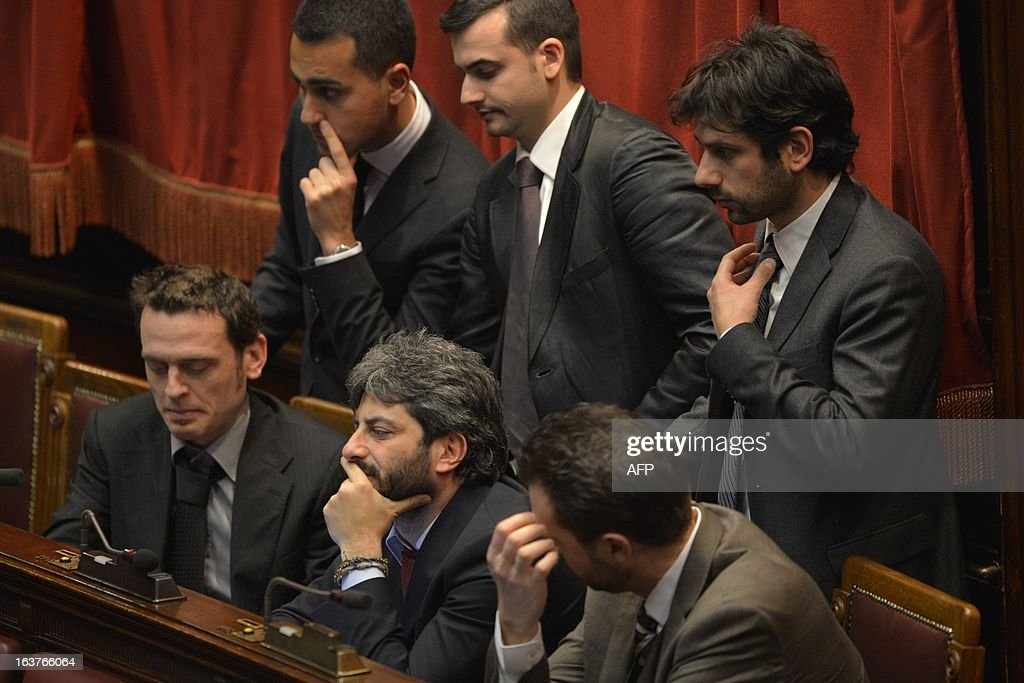 Five Star Movement newly elected member of parliament Roberto Fico (C) and colleagues react during the vote of the first session of Italian lower-house on March 15, 2013 in Rome. General election in Italy took place on February 26 but as a majority in both chambers of parliament is required to form a government, Italy is left in a state of limbo with a hung parliament that is unprecedented in its post-war history.