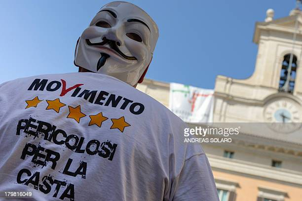 Five Star Movement party activist looks at Five Star Movement party deputies as they stand next to a banner reading 'The constitution belongs to...
