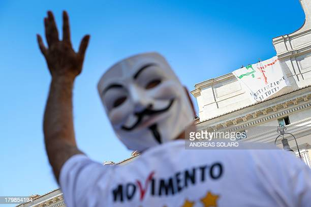 Five Star Movement party activist waves at Five Star Movement party deputies as they stand next to a banner reading 'The constitution belongs to...