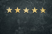 Five stars in a row on a black rustic cement boards. Conceptual of service rating and quality of trade. Top view, copy space for your text.