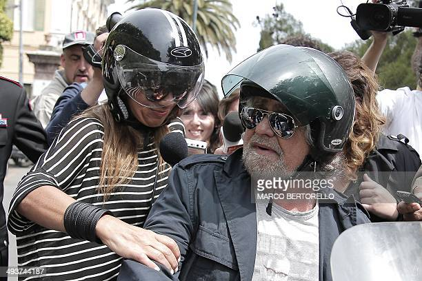 Five Stars movement's leader and former comedian Beppe Grillo arrives with his wife Parvin Tadjk to vote at a polling station in Saint Ilario near...