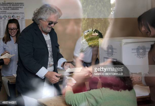 Five Stars movement's leader and former comedian Beppe Grillo takes back his documents after casting his ballot for the European parliament elections...