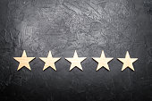 five stars on a dark background. The concept of rating and evaluation. The rating of the hotel, restaurant, mobile application. Quality service, buyer choice. Success in business