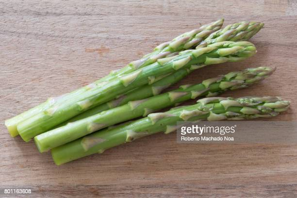 Five sticks of healthy green asparagus on a wooden table
