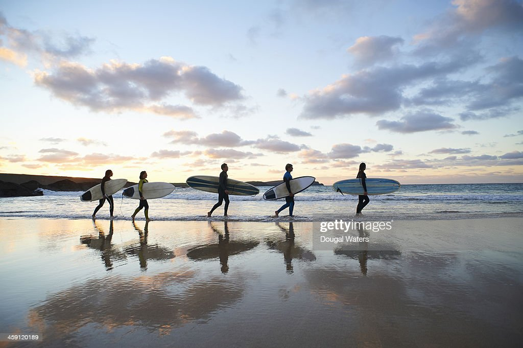 Five surfers walk along beach with surf boards.