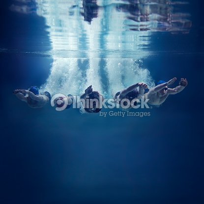 Five swimmers jumping together into water, underwater view : Stock Photo