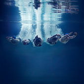 Five, young swimmers are jumping in direction of the camera. This is underwater shoot. There are 3 girls and 2 boys. They wear caps, swimming goggles and swimwears. The swimmers just entered the water